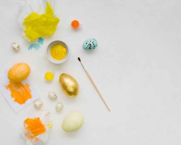 イースターのための黄金の卵とブラシでペイントのフラットレイアウト
