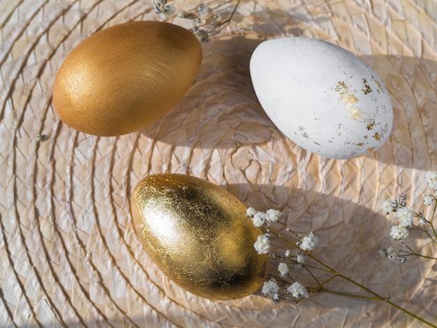 Вид сверху золотых цветных пасхальных яиц на подставке с гипсофилой