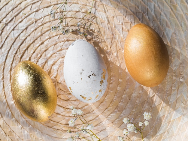 Вид сверху золотых цветных пасхальных яиц на подставке