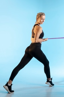 Вид сбоку женщина упражняется с резинкой