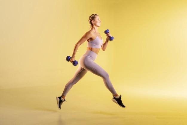 Тренировка молодой женщины с весами