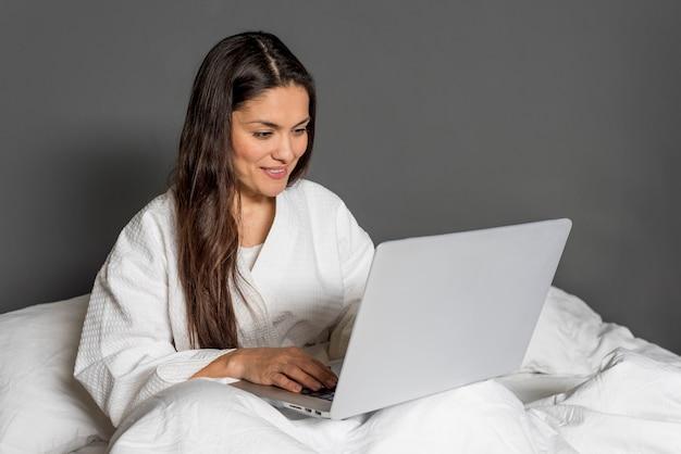 ラップトップが付いているベッドで高角の女性