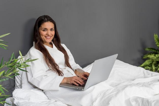 ラップトップが付いているベッドでスマイリー女性