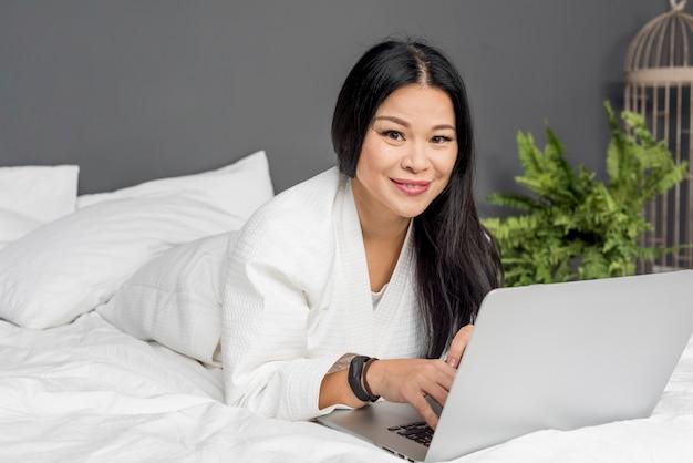 ラップトップが付いているベッドに横たわる美人