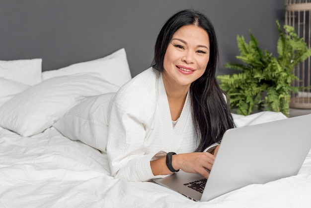ラップトップが付いているベッドに横たわる美しい女性