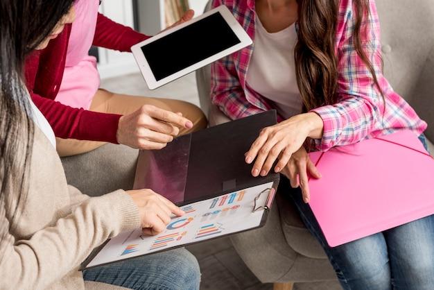 Крупный план женщин с планшета и буфера обмена анализа