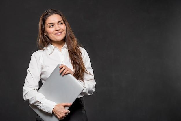 Низкий угол женщина, держащая ноутбук