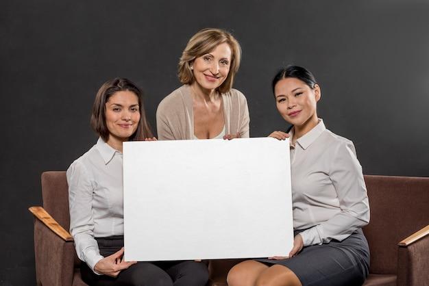 空白の紙のシートを保持している女性のグループ