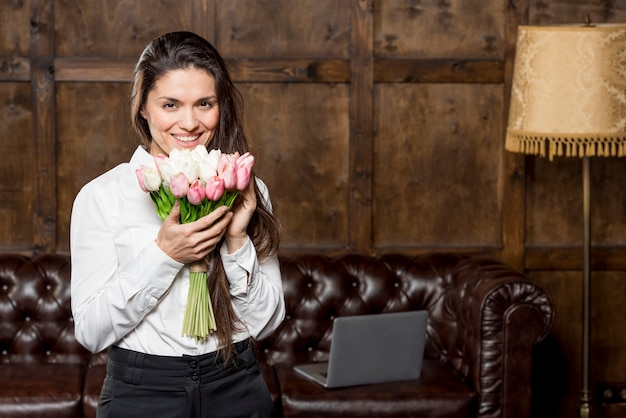 花の花束を保持している美しい女性