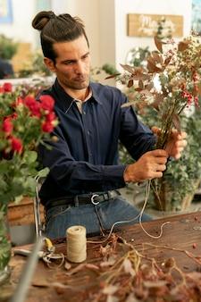 Садовник мужчина с длинными волосами держит букет цветов