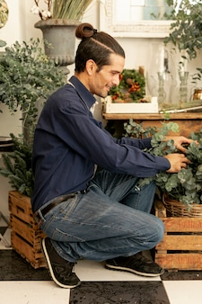 植物を配置する長い髪を持つ庭師男