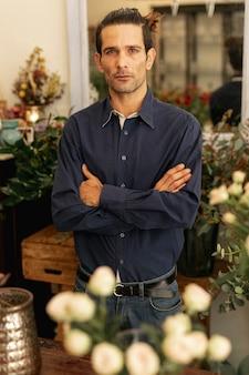 腕を組んで立っている経験豊富な花屋