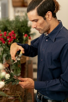花屋の男性の切り花の茎を横に