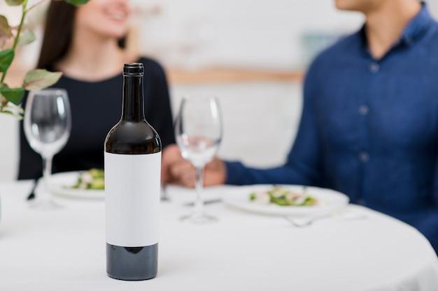 ワインのボトルとバレンタインの日を祝うカップル