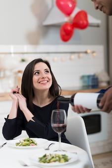 彼のガールフレンドのためにグラスにワインを注ぐ正面男