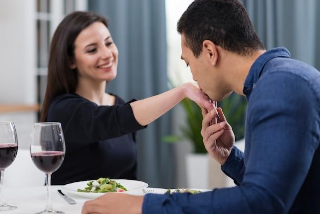 彼のガールフレンドの手にキスをする男性