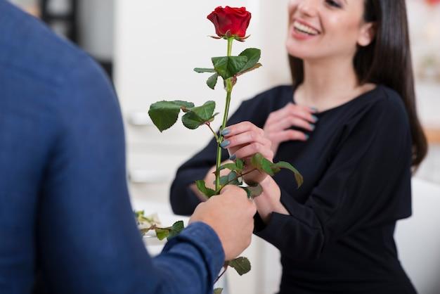 Мужчина предлагает своей девушке розу на день святого валентина