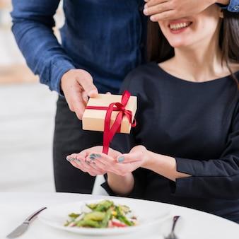 彼女に贈り物のクローズアップを与える前に彼のガールフレンドの目を覆っている男