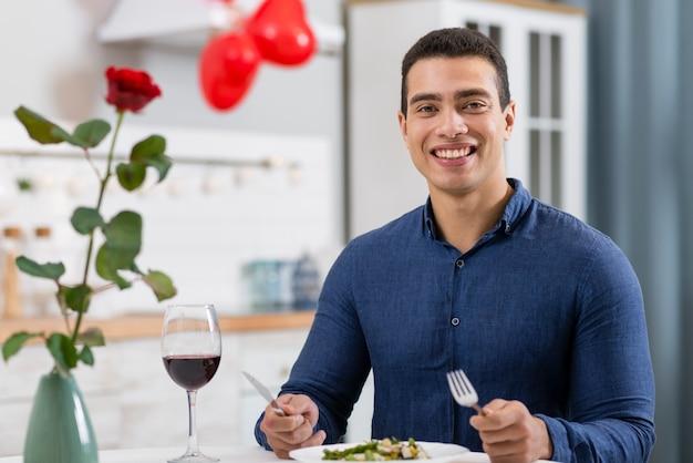 バレンタインの日に夕食を食べているスマイリー男