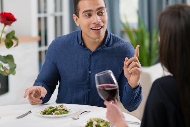 バレンタインのディナーで彼の婚約者と話している男性