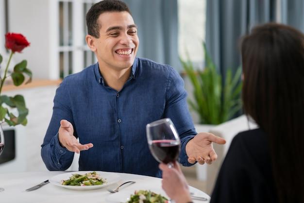 バレンタインのディナーで彼のガールフレンドと話している男性