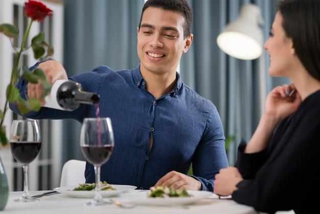 ロマンチックなディナーを一緒に持っている正面のカップル
