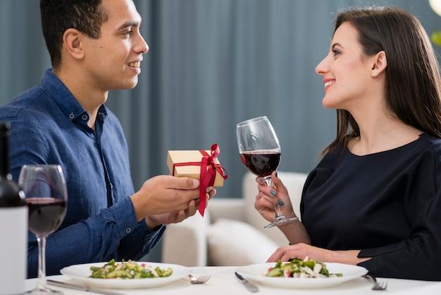 バレンタインの日に彼のガールフレンドに贈り物を与える男
