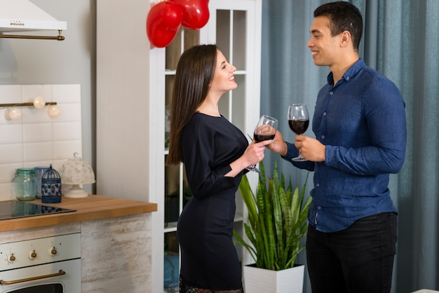 台所でワインのグラスを持っているカップル