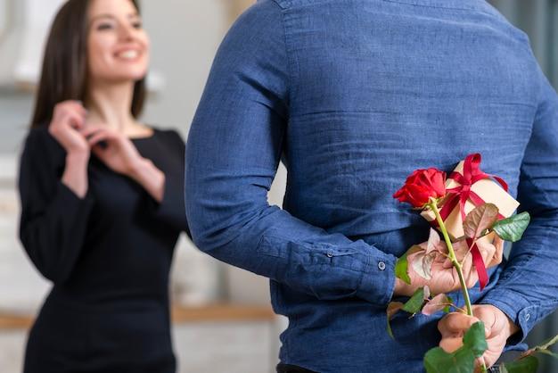 バレンタインデーのギフトのクローズアップで妻を驚かせる男