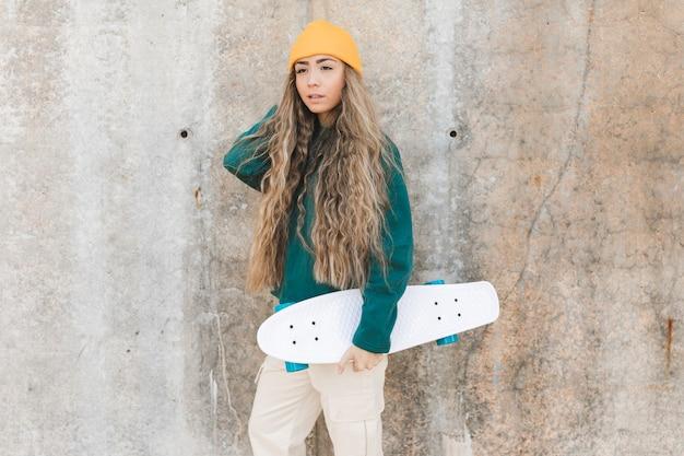 Вид сбоку молодая женщина со скейтбордом