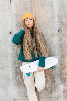 Высокий угол молодая женщина со скейтбордом