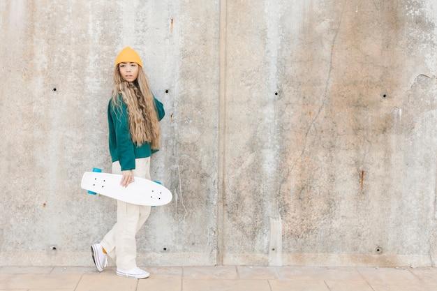 スケートボードを持つコピースペース若い女性