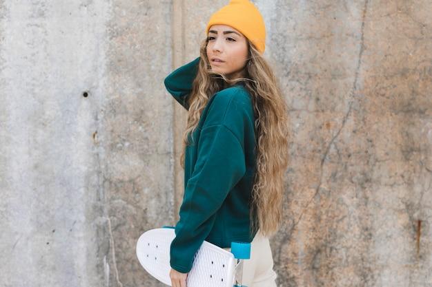 Женщина высокого угла с скейтбордом