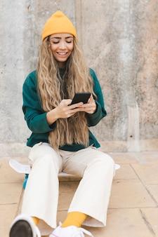 携帯電話を使用しながらスケートボードに座っている笑顔の女性