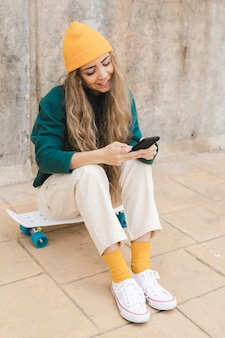 Высокий угол смайлик женщина, сидящая на скейтборде