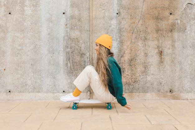 Высокий угол женщина езда скейтборд