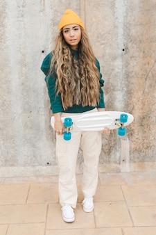 スケートボードを保持している高角度の女性