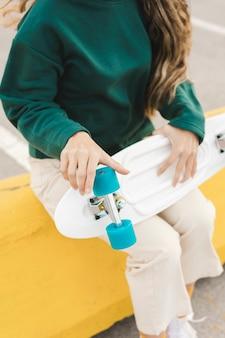スケートボードの車輪をチェックするクローズアップ女性
