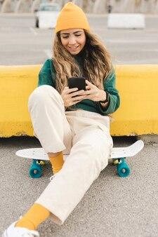 電話を使用してスケートボードのスマイリー女性