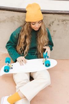 Женщина высокого угла смотря скейтборд
