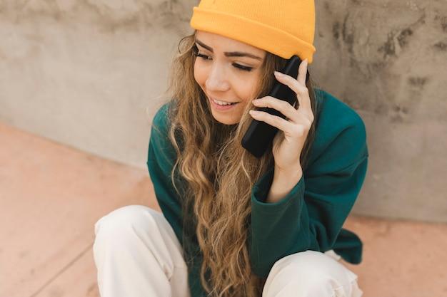 Женщина на скейтборде разговаривает по телефону
