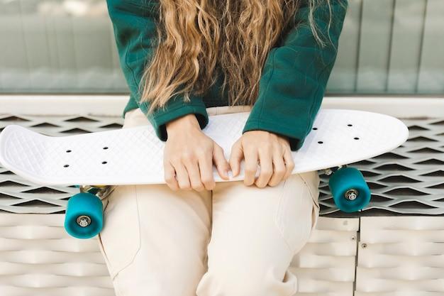 Макро молодая женщина с скейтборд