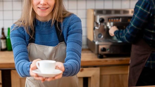 コーヒーを保持しているバリスタの正面図