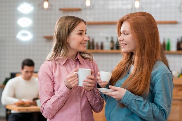 Вид спереди друзей, пьющих кофе