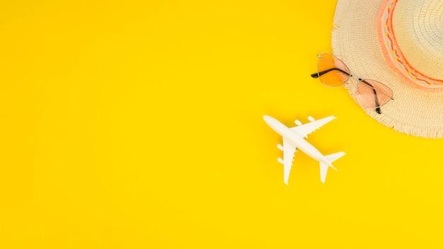 Скопируйте игрушку космического самолета рядом со шляпой и солнцезащитными очками