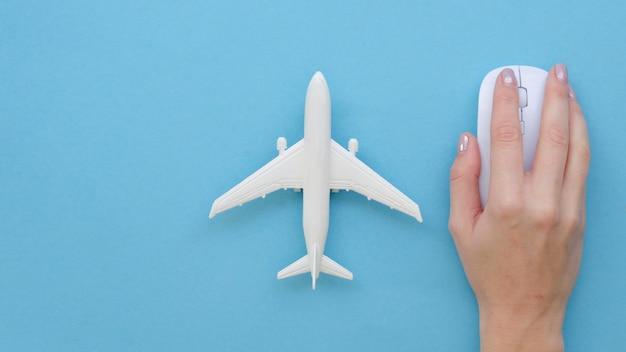 飛行機のおもちゃの横にあるマウスを持つ手