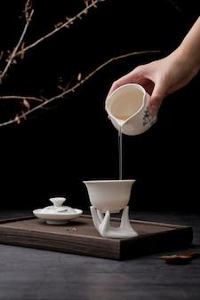Крупным планом человек наливает напиток в белой чашке