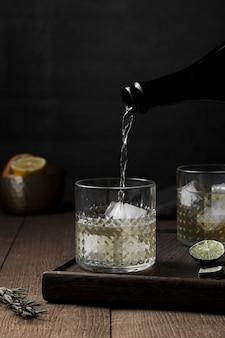Напиток наливая в стакан с кубиками льда