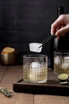Мужчина крупным планом кладет кубик льда в стакан