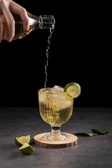 Крупным планом человек наливает напиток в стакан